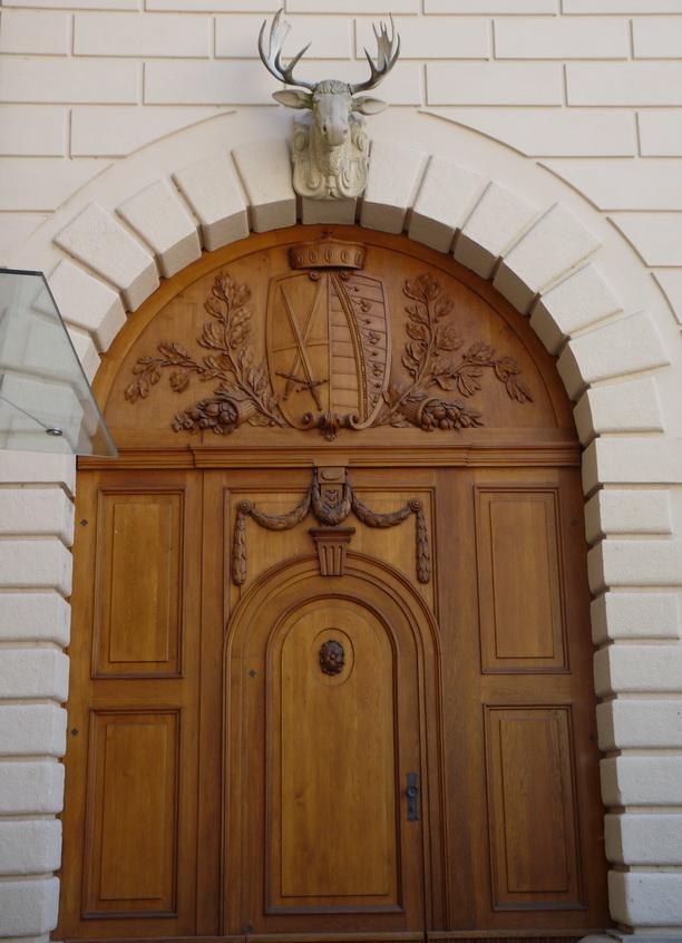 Массивные неприступные деревянные двери в одном из зданий и голова оленя над ними.